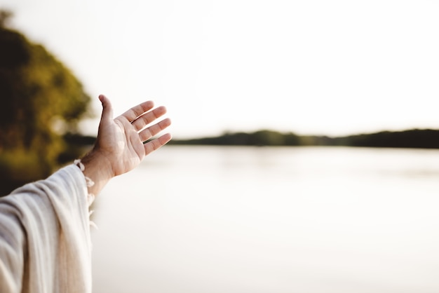 Imagem aproximada de uma pessoa vestindo uma túnica bíblica com a mão para cima
