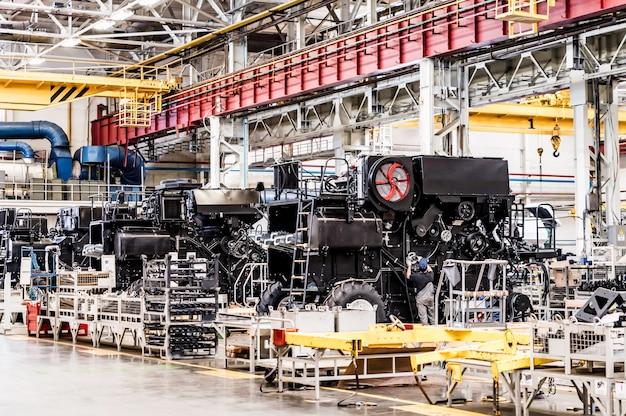 Imagem aproximada do homem na sala de montagem de uma grande fábrica de tratores e colheitadeiras