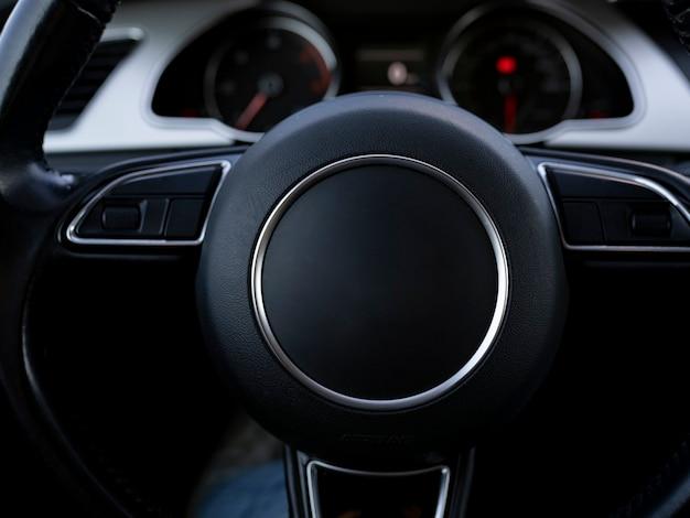 Imagem aproximada do volante e do painel de controle de um carro