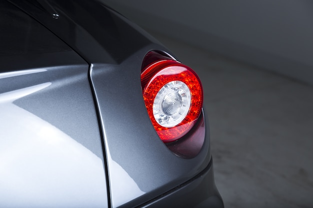 Imagem aproximada dos faróis de um carro prateado moderno