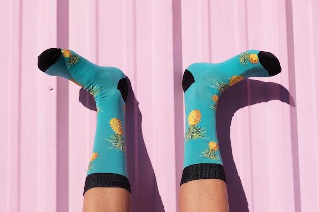Imagem aproximada dos pés de uma pessoa usando meias azuis com design de abacaxi