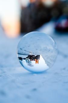 Imagem aproximada ou uma gota d'água no solo nevado refletindo uma parte da cidade