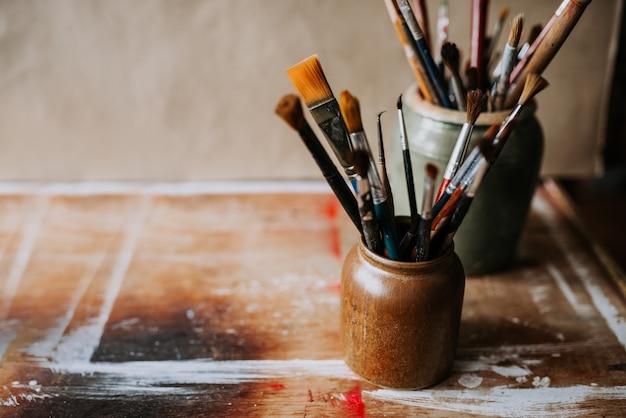 Imagem artística de pincéis de pintura em um frasco de cerâmica.