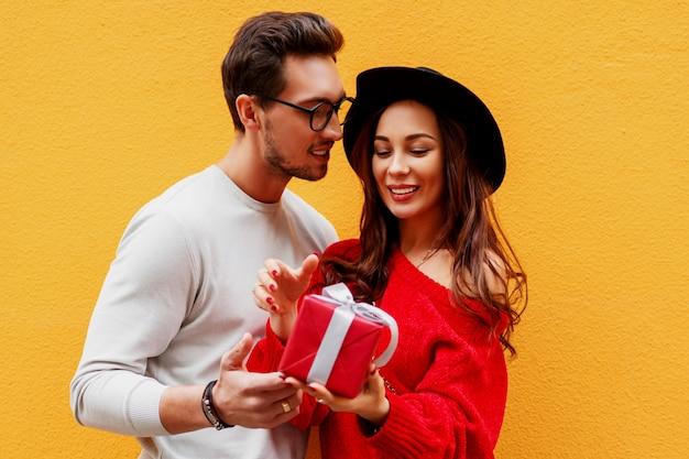 Imagem ascendente próxima do estúdio de casal apaixonado. cara bonito dá um presente para sua namorada