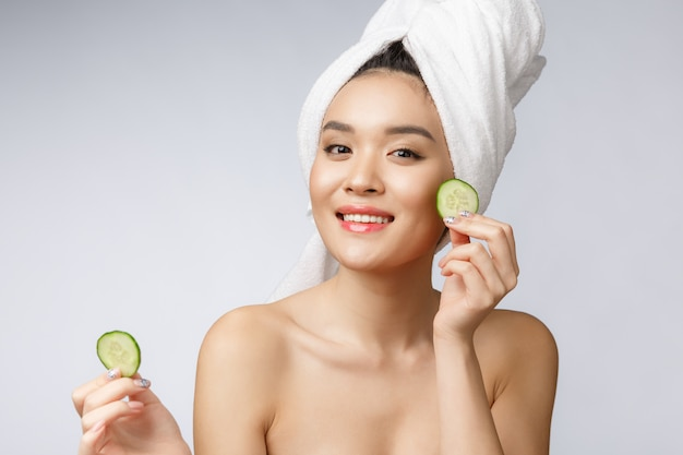 Imagem asiática nova dos cuidados com a pele das mulheres da beleza com o pepino no estúdio branco do fundo.