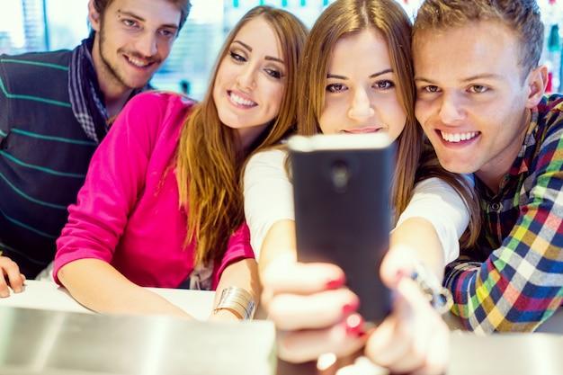 Imagem autêntica de pessoas novas e novas com bom tempo juntos usando celular