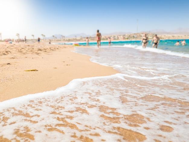 Imagem bonita das ondas do mar calmo rolando na praia do mar em um dia ensolarado. plano de fundo perfeito para ilustrar férias de verão, viagens ou férias. lugar para o seu texto. copie o espaço