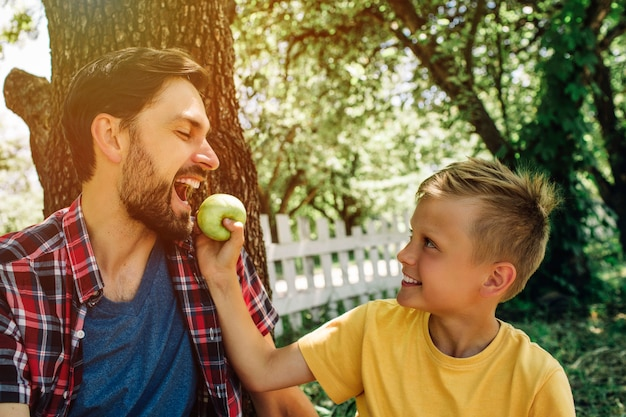 Imagem bonita de pai e filho sentados juntos lá fora debaixo da árvore. garoto está segurando uma maçã enquanto seu pai está mordendo um pedaço dela.