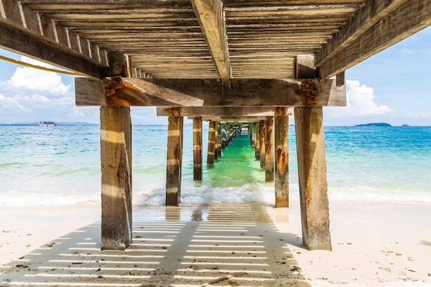 Imagem bonita que espirra a onda do mar sob o concreto velho e a ponte de madeira.