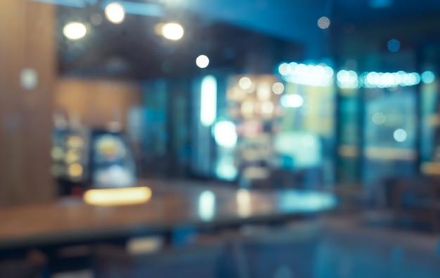 Imagem borrada abstrata de café ou restaurante com fundo de luzes bokeh à noite