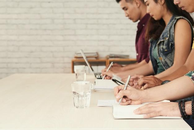 Imagem borrada da linha de estudantes ocupados escrevendo teste em sala de aula