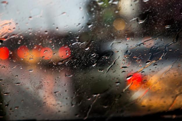 Imagem borrada da visão do trânsito através de um pára-brisas do carro coberto de chuva