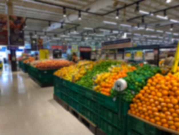Imagem borrada de barracas de frutas e vegetais em um supermercado
