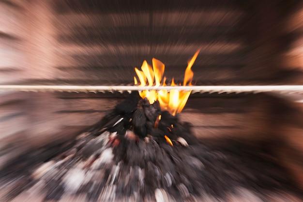 Imagem borrada de carvão queimando no churrasco
