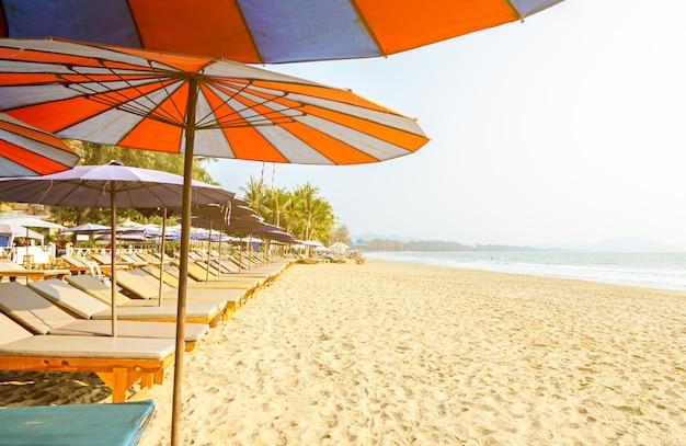 Imagem borrada de espreguiçadeiras e guarda-chuva em uma praia tropical