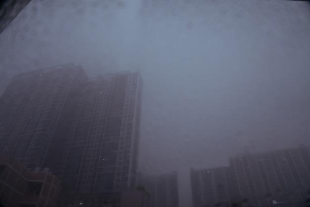 Imagem borrada de gotas de chuva no espelho com edifícios e fundo da estrada