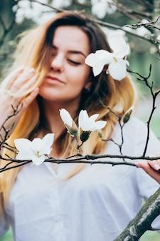 Imagem borrada de uma menina bonita, desfrutando de árvores florescendo magnólia, olhos fechados