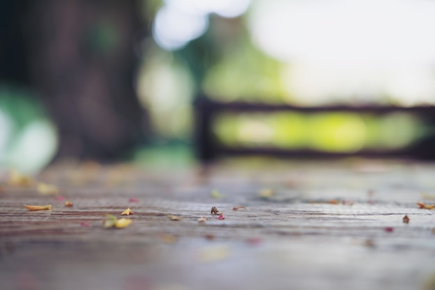 Imagem borrada e bokeh de folhas de sucata e flores na mesa de madeira