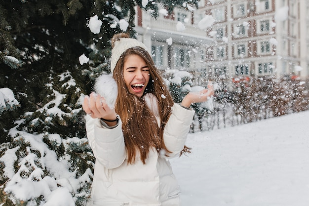 Imagem brilhante animada de alegre incrível inverno bonito mulher se divertindo com neve ao ar livre na rua. momentos felizes, brincar com flocos de neve, curtir, emoções positivas.
