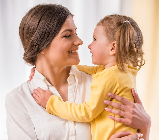 Imagem brilhante de abraçar a mãe e a filha pequena.