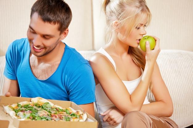 Imagem brilhante de casal comendo alimentos diferentes (foco na mulher)