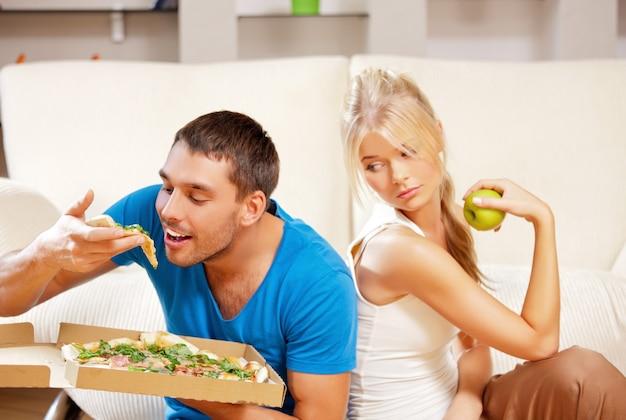 Imagem brilhante de casal comendo alimentos diferentes (foco no homem)