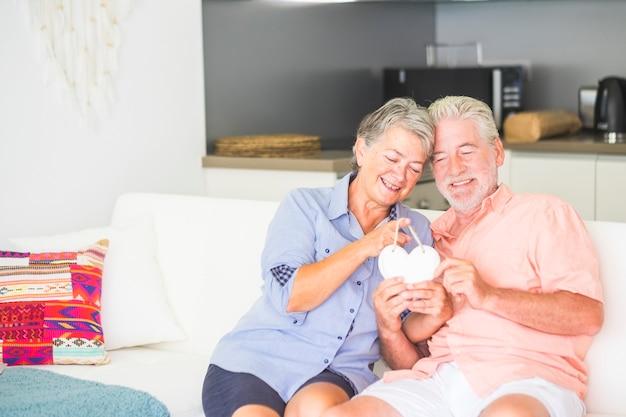 Imagem brilhante de casal de homem e mulher caucasianos felizes em casa sentados no sofá com cozinha brincando com uma lareira branca junto com amor