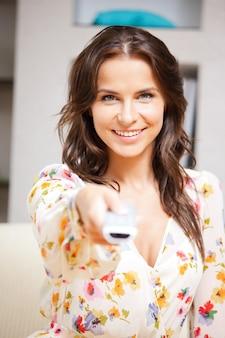 Imagem brilhante de mulher feliz com controle remoto de tv