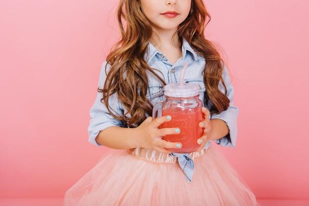 Imagem brilhante elegante de menina bonitinha com longos cabelos morenos, em saia de tule segurando um copo com suco isolado no fundo rosa. infância feliz com uma bebida adorável, anos jovens saborosos