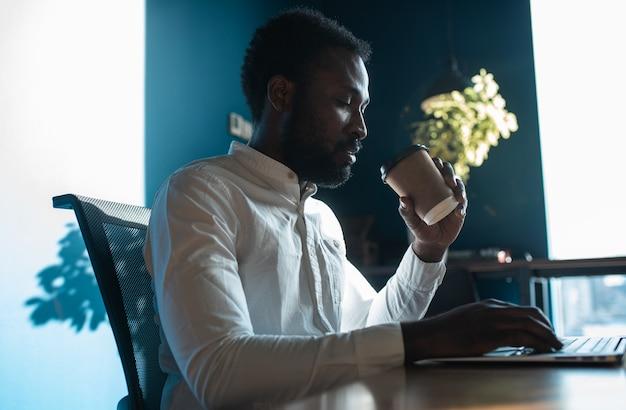 Imagem cinematográfica de um jovem belo homem de negócios. retrato de um funcionário em seu escritório