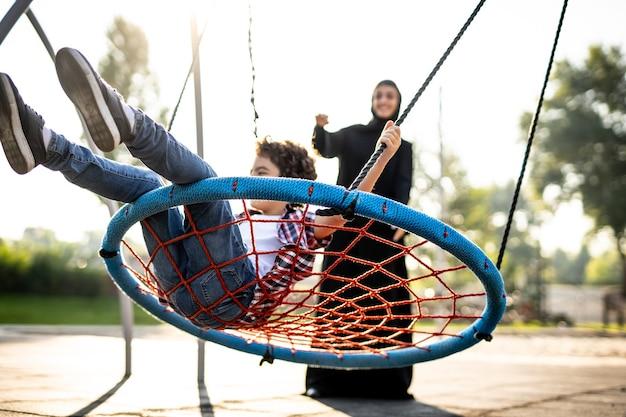 Imagem cinematográfica de uma mulher dos emirados com seus filhos se divertindo no parquinho