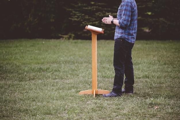 Imagem com foco raso de um homem perto de um palestrante com um livro aberto