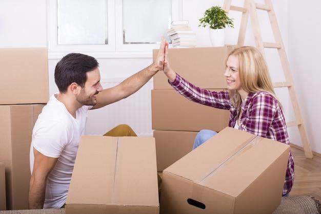 Imagem com foco superficial de um jovem casal fazendo reparos em sua casa