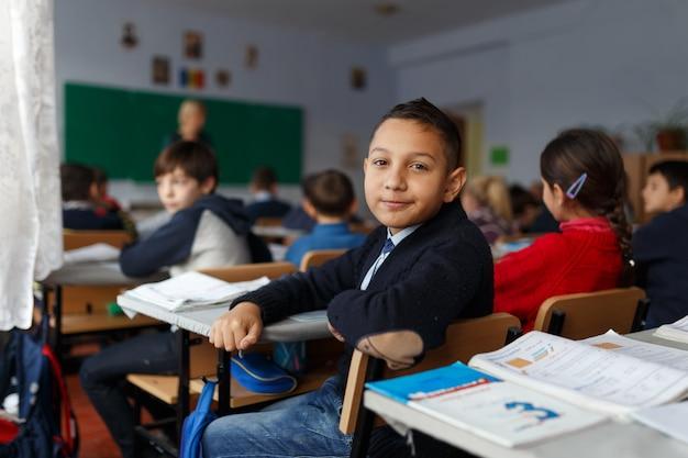 Imagem com um menino sentado em sua mesa na escola