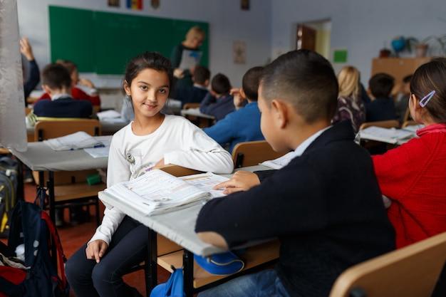 Imagem com uma garota e seu colega no primeiro dia de volta às aulas