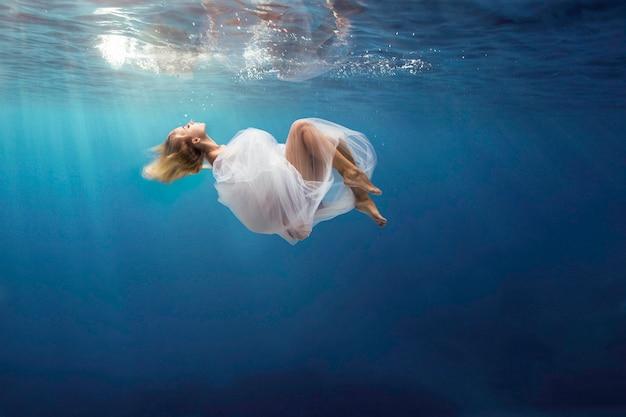 Imagem com uma jovem nadando artisticamente na piscina