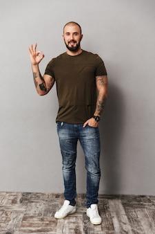 Imagem completa de careca com barba vestindo casual olhando e mostrando tudo certo sinal, isolado sobre a parede cinza