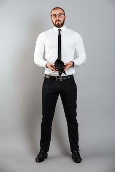 Imagem completa do empresário frustrado de óculos e terno mostrando sua bolsa vazia, isolada sobre parede cinza