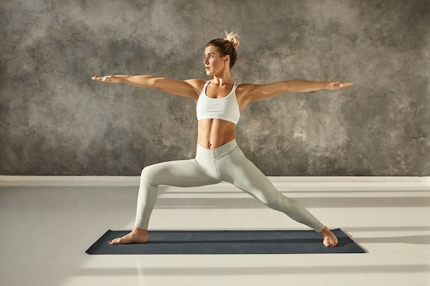 Imagem completa lateralmente de uma jovem atraente e musculosa praticando hatha ioga na academia, descalça em uma esteira na pose de virabhadrasana 2 ou guerreiro dois, com expressão facial concentrada
