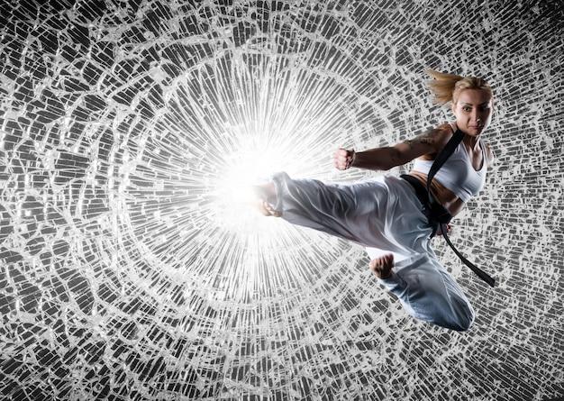 Imagem composta de caratê vestindo roupas esportivas brancas e faixa preta, quebrando vidros no salto