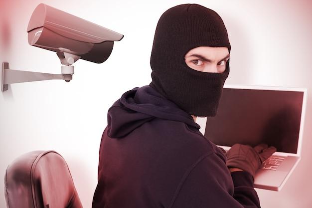 Imagem composta de um hacker sentado e hackeando um laptop