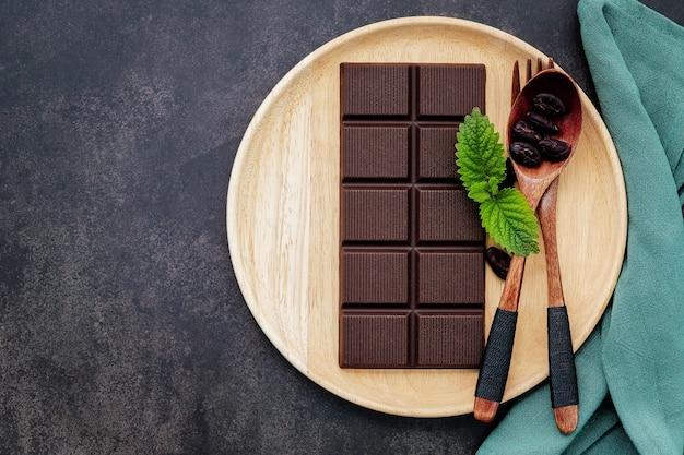 Imagem conceitual de comida com chocolate escuro e garfo no fundo escuro de concreto.