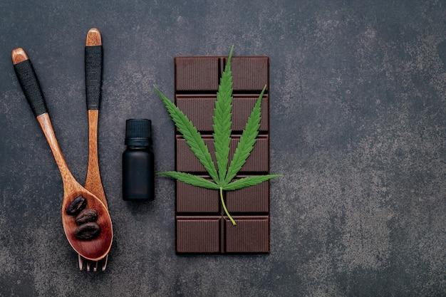 Imagem conceitual de comida de folha de cannabis com chocolate escuro e um garfo no concreto escuro.