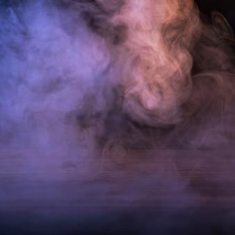 Imagem conceitual de fumaça multicolorida isolada em fundo preto escuro e mesa de madeira. Foto Premium