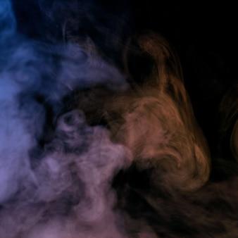 Imagem conceitual de fumaça multicolorida isolada em fundo preto escuro e mesa de madeira.