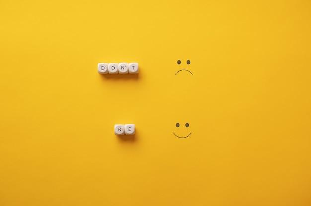 Imagem conceitual de incentivo a ser positivo com uma mensagem motivacional sobre fundo amarelo.