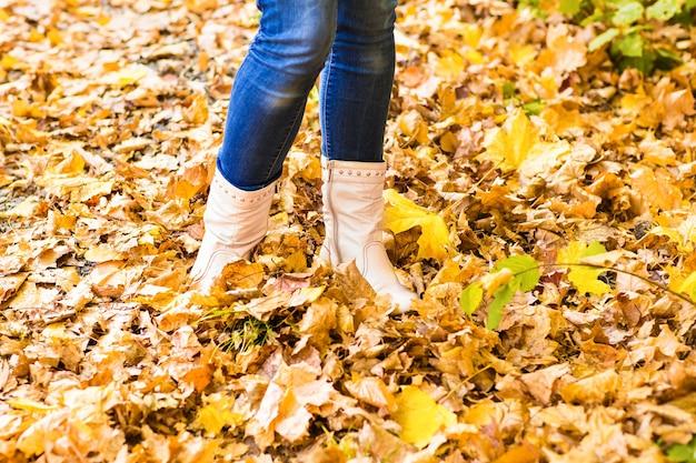 Imagem conceitual de pernas em botas nas folhas de outono. sapatos de pés caminhando na natureza.