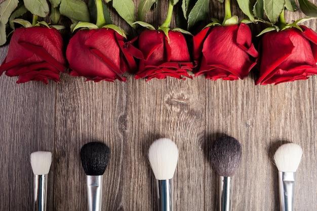 Imagem conceitual de pincéis de maquiagem ao lado de rosas em fundo de madeira