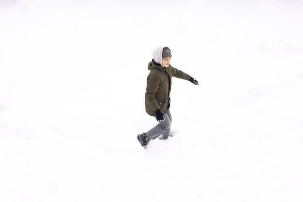 Imagem conceitual do menino correndo deitado no chão coberto de neve isolada no branco, vista superior do drone