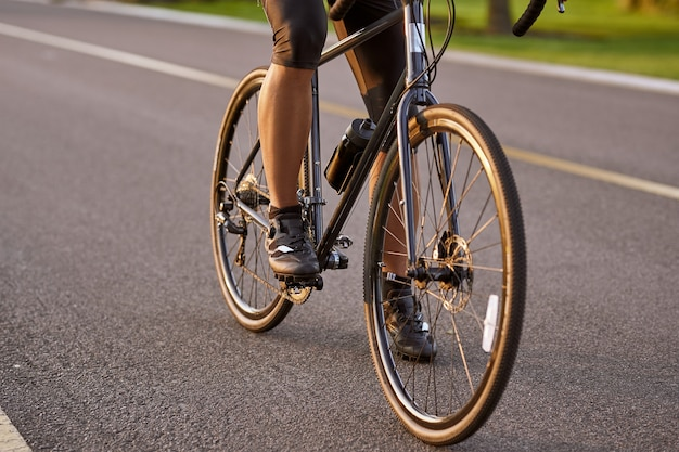 Imagem cortada de um homem andando de bicicleta ao ar livre com foco nas pernas masculinas